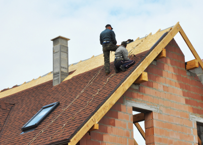 building contractors putting the asphalt roofing
